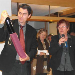 Uta Böckel überreicht Dr. Sascha Raabe eine Flasche Wein
